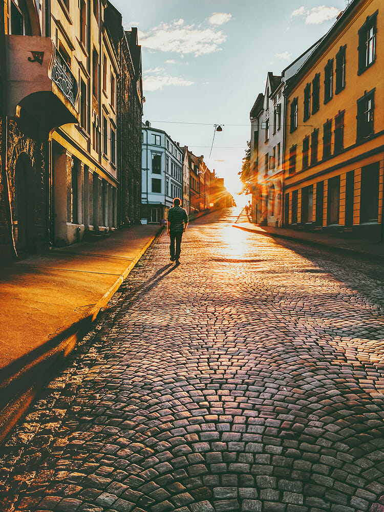 man male wandering town deserted evening sunset yellow orange shilouette photography cobbles vintage retro old long shadow travel photography