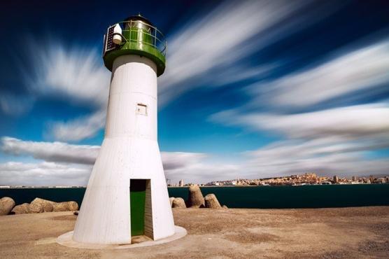 lighthouse green white blue sky clouds blur slow shutter speed