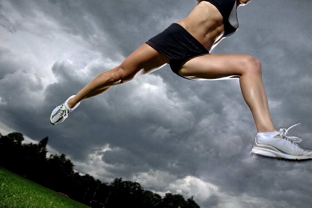 photograph of woman jumping over hurdle in storm