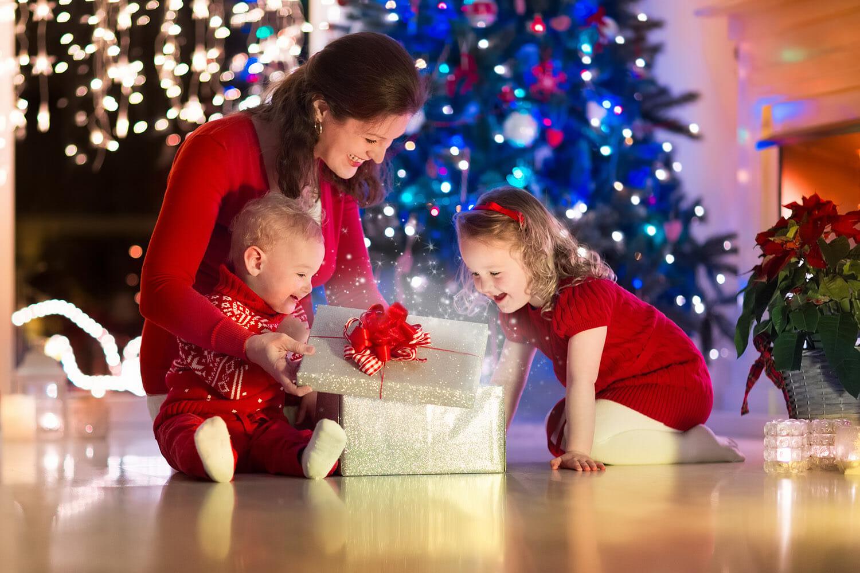 christmas eve parent mother children presents tree lights twinkling