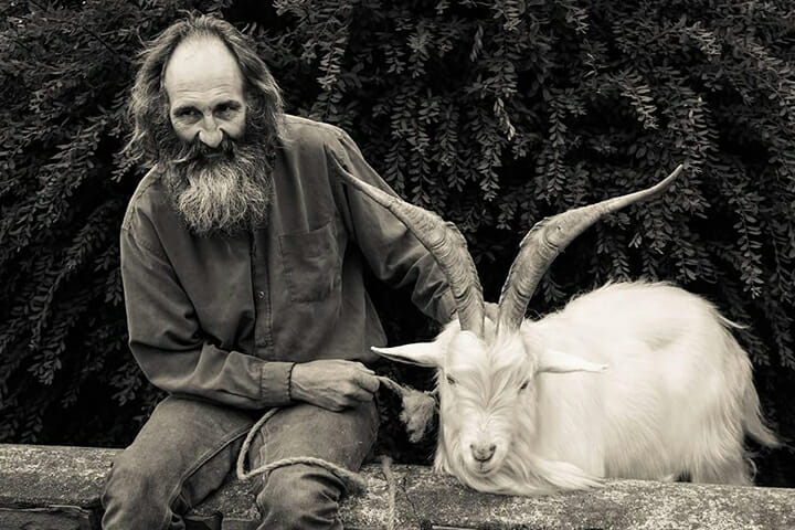 man sat with goat on a wall street photography portrait city people camera subject light how to tutorial guide