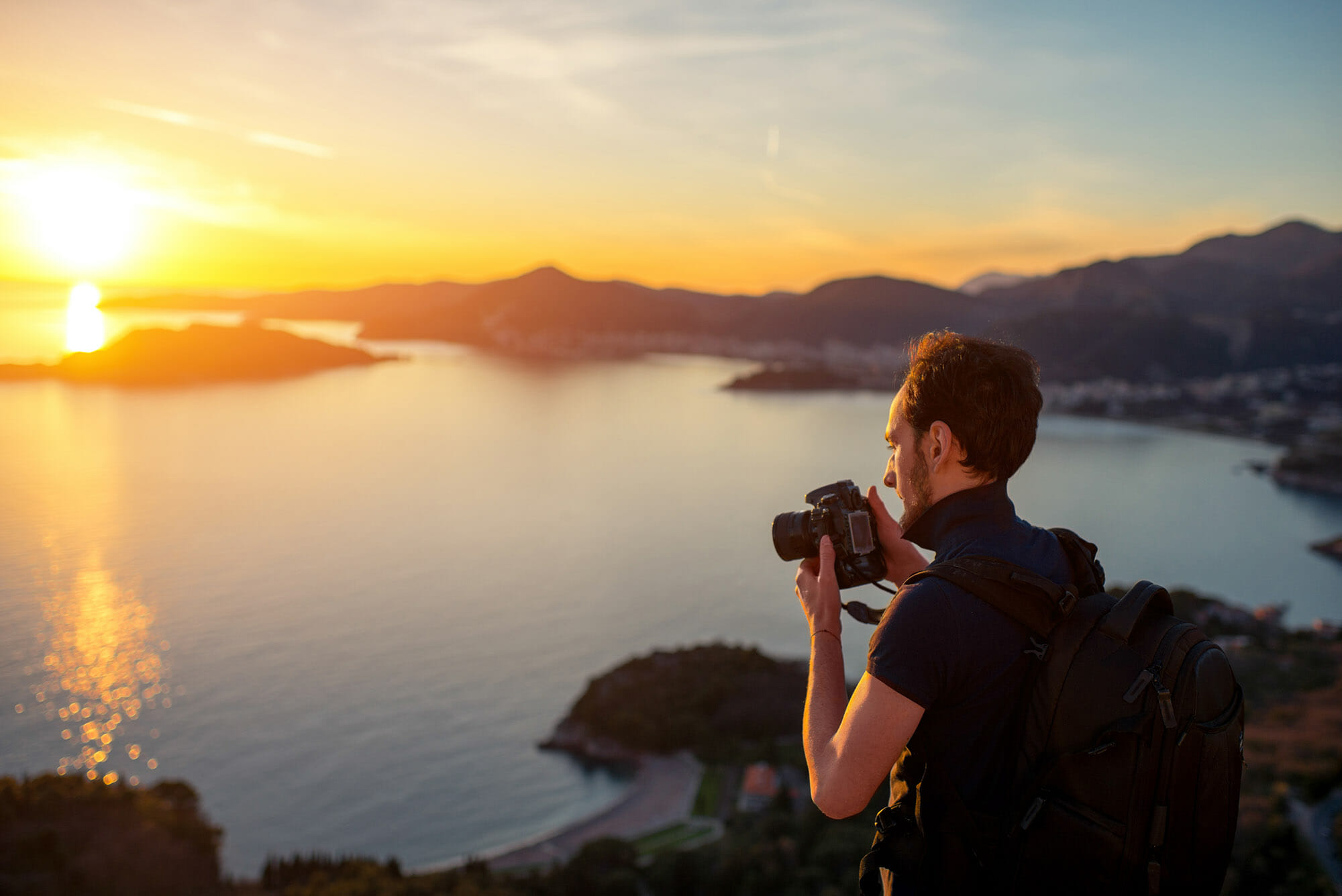 man camera cliff top sunset polo shirt wind taking photographs of landscape