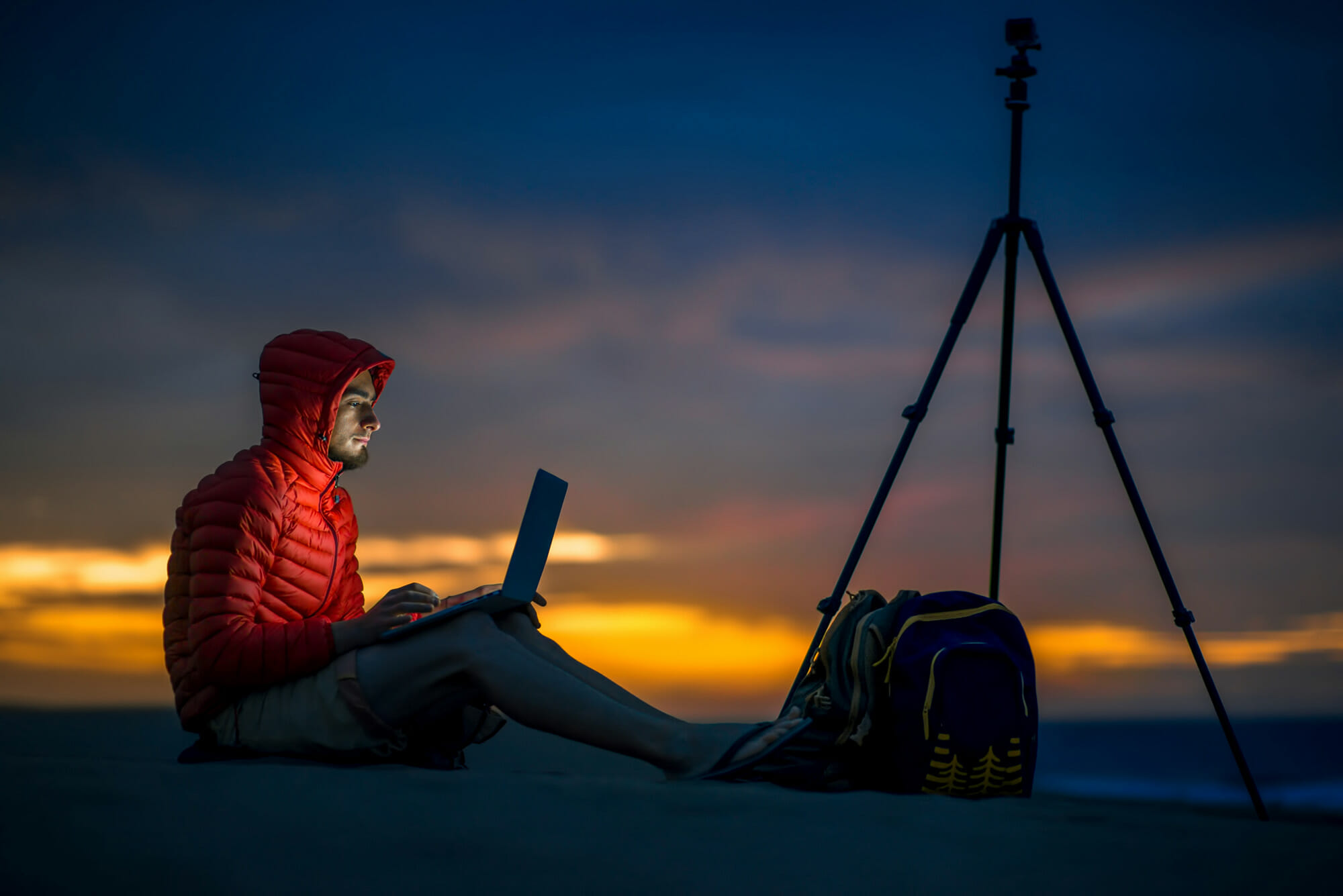 man sat in red jacket editing pictures on laptop night time sunset with tripod