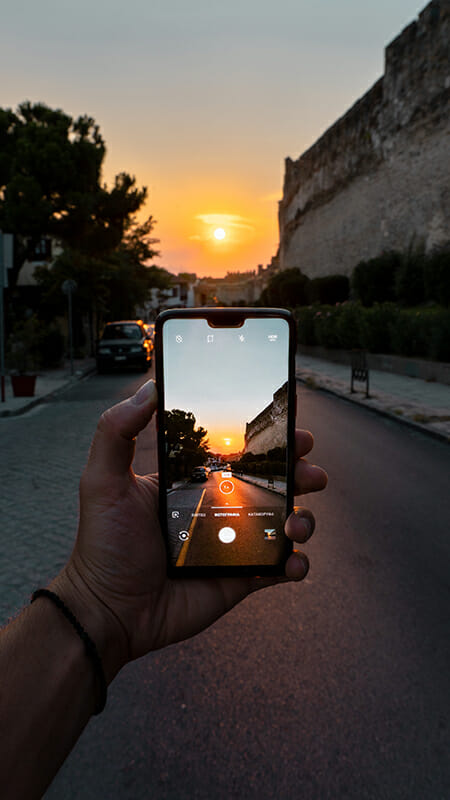 smartphone taking picture of sunset
