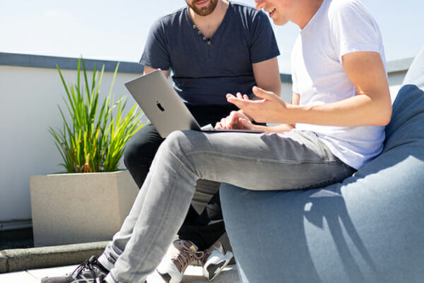 two males talking over a laptop