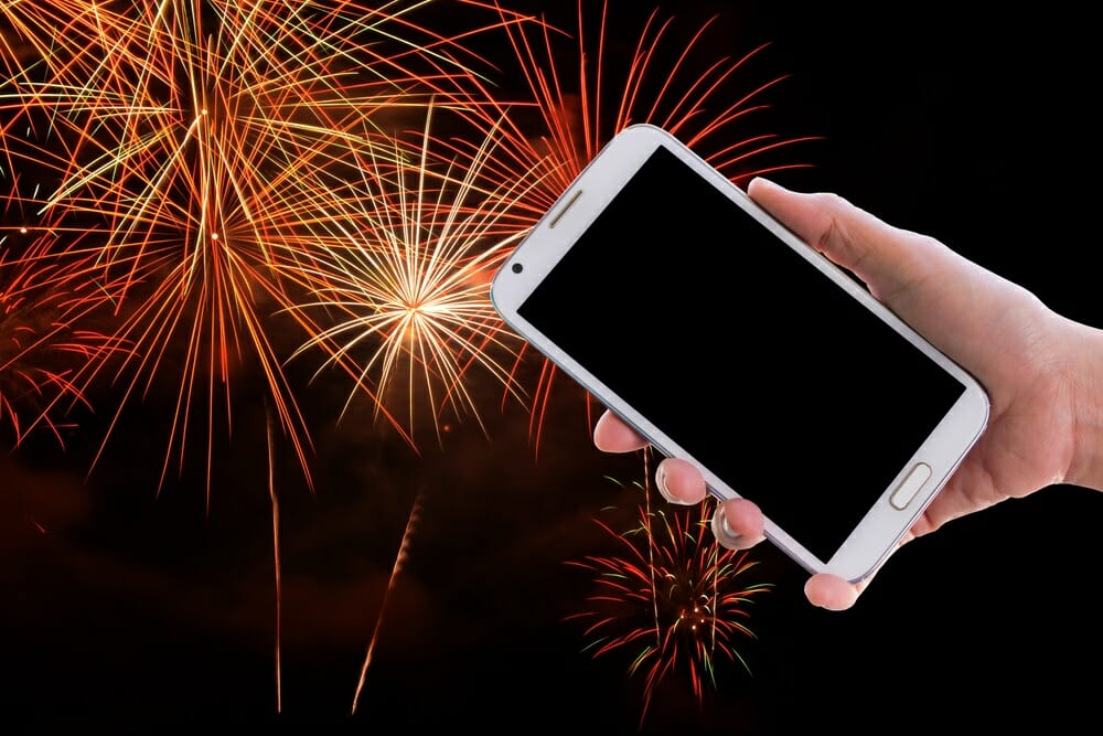 smartphone being held in front of fireworks