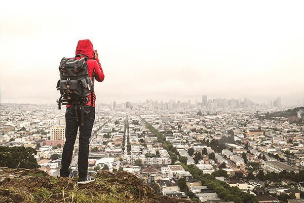 photographer on cliff edge overlooking city