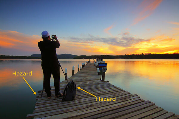 photographer stood on jetty boat in distance