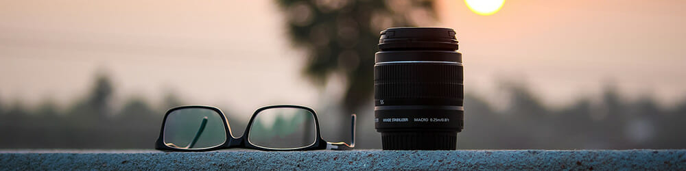 glasses and a macro lens with a sunset behind