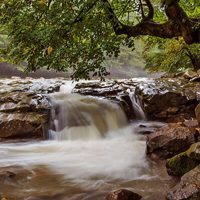 water slow shutter speed over rocks on river landscape photography