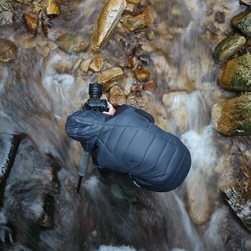 photographer rushing water camera rocks