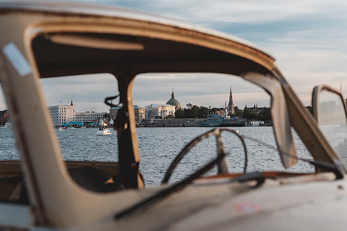 looking through an old car with no windows city framed in the background
