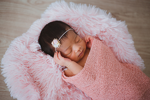 baby asleep lying on a pink fluffy cushion