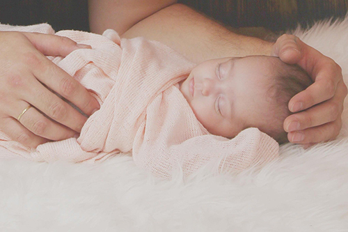 baby wrapped in pink blanket asleep soft light