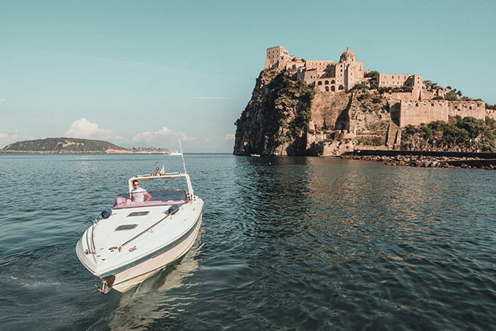a man on a speedboat in ischia expensive camera equipment