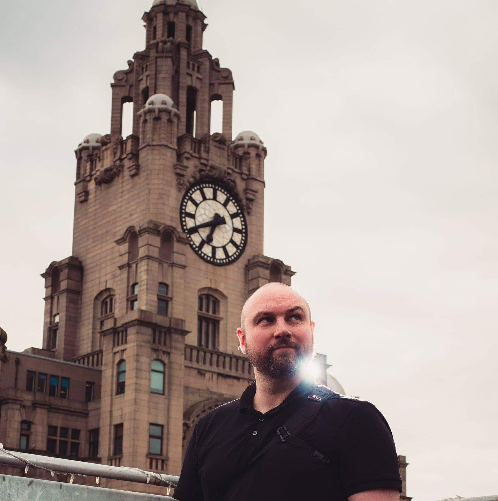 a wedding photographer standing infront of the liver buildings