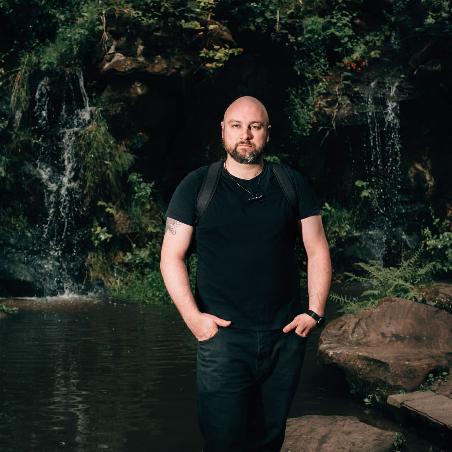 a wedding photographer standing in front of a waterfall with his hands in his pockets
