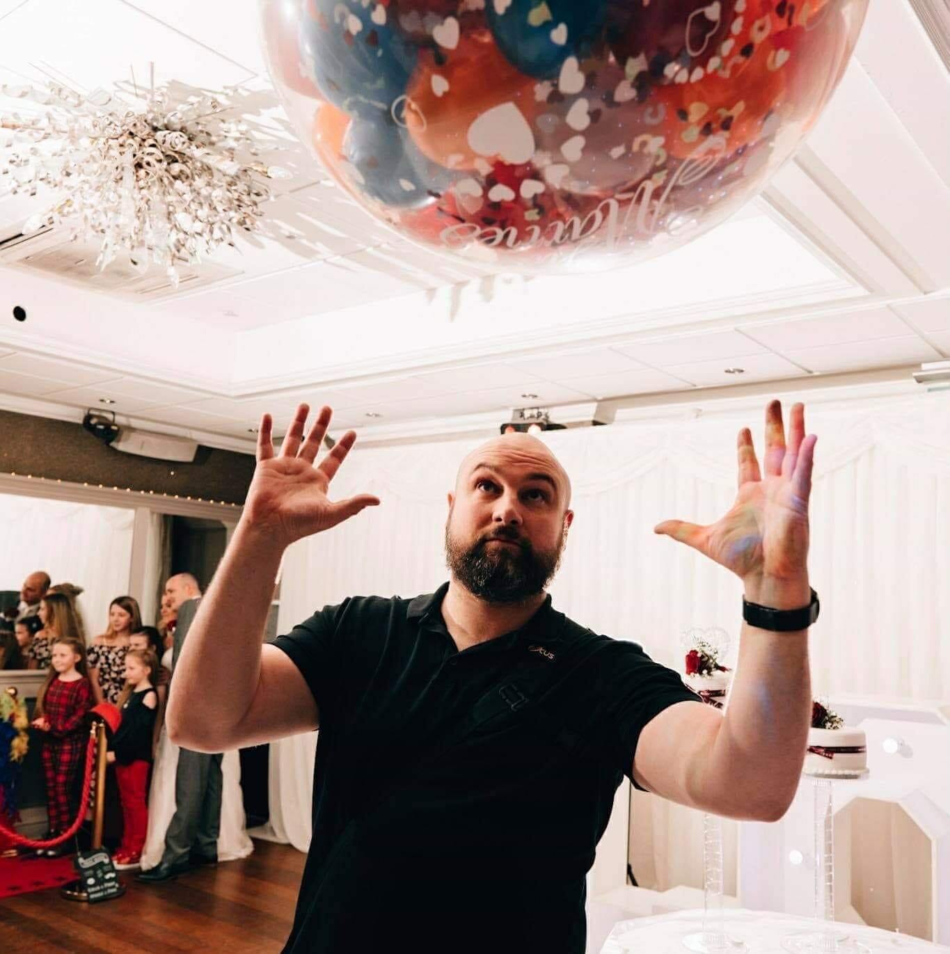 a wedding photographer trying to catch a balloon