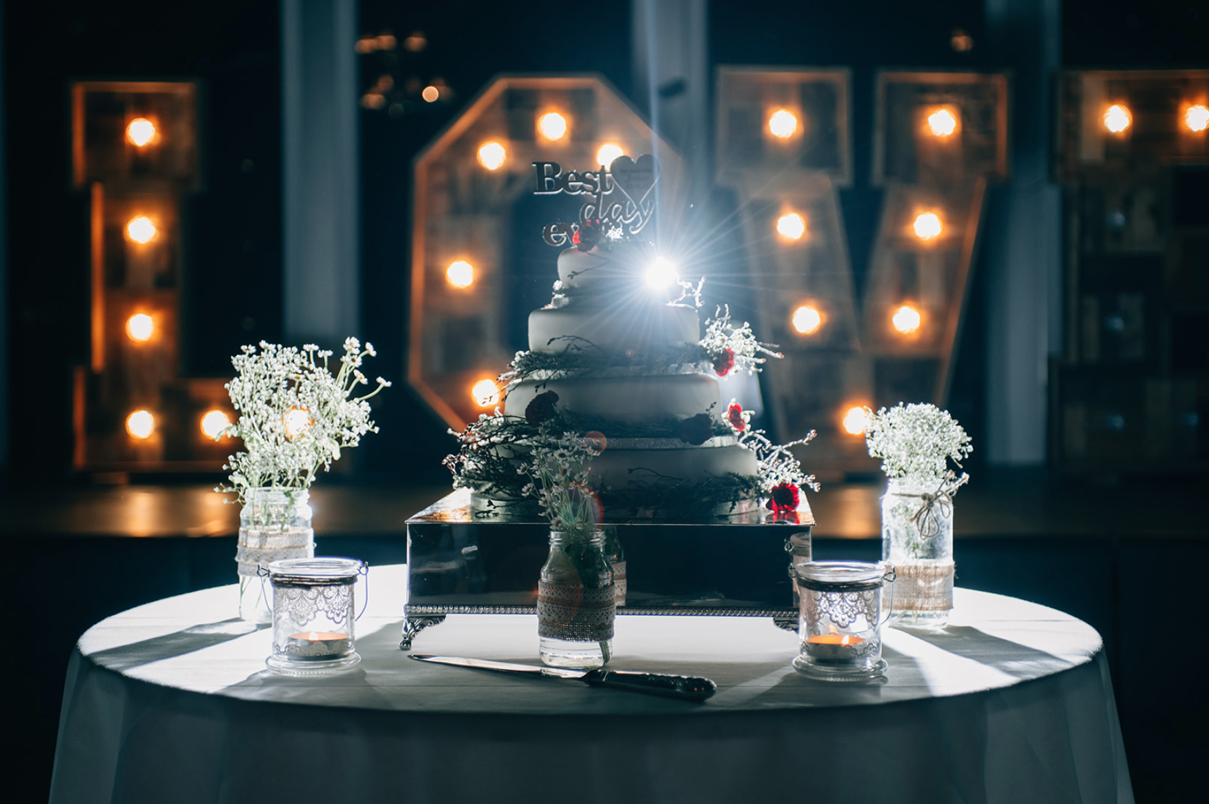 a wedding cake with a lens flare behind it