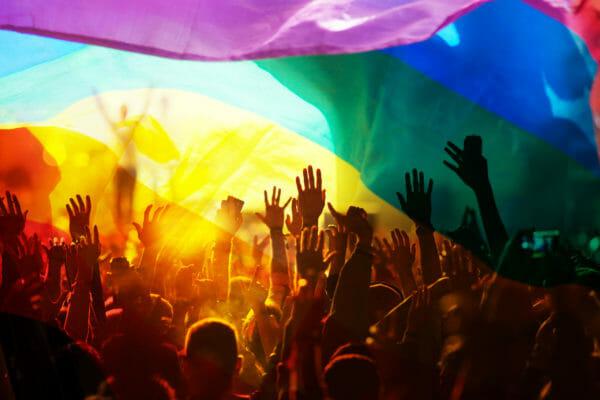 pride flag over a non socially distanced crowd LGBTQ+ photography