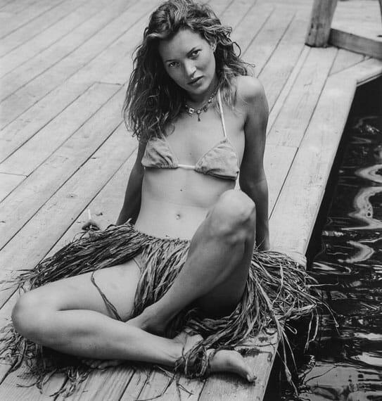 Kate moss sitting down with a bikini on