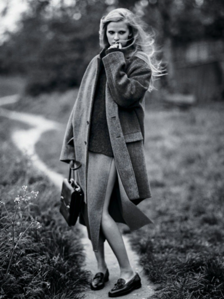 a woman with a coat and briefcase touching her face