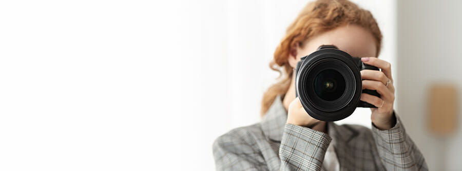 lady with camera red hair pointing at audience space to left