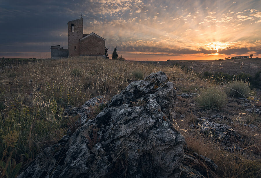 building in background rock in foreground sunset landscape