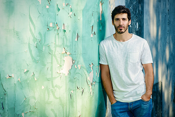 posing men blog image man leaning against a wall paper distressed in white tshirt and jeans