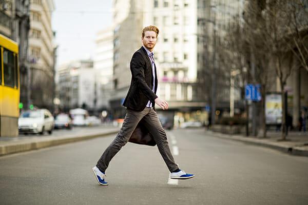 posing men blog image man walking acorss the street holding a bag