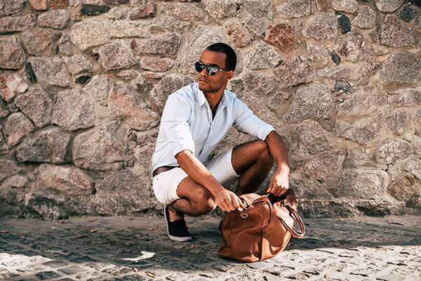 posing men blog image man wearing sunglasses looking in a bag crouched down