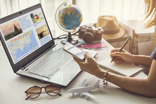 how to motivate for photographers blog image lady planning a trip in front of laptop with camera travel
