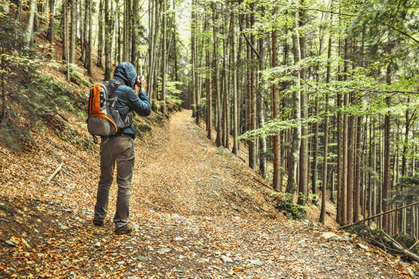 how to motivate for photographers blog image man taking a photograph in woodland blue coat orange bag