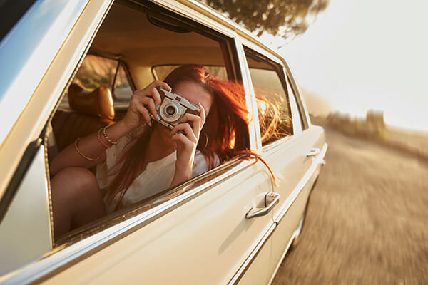 female leaning out of a car window taking a picture