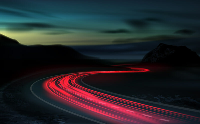 shutter speed red trail light trailing through a countryside road at night