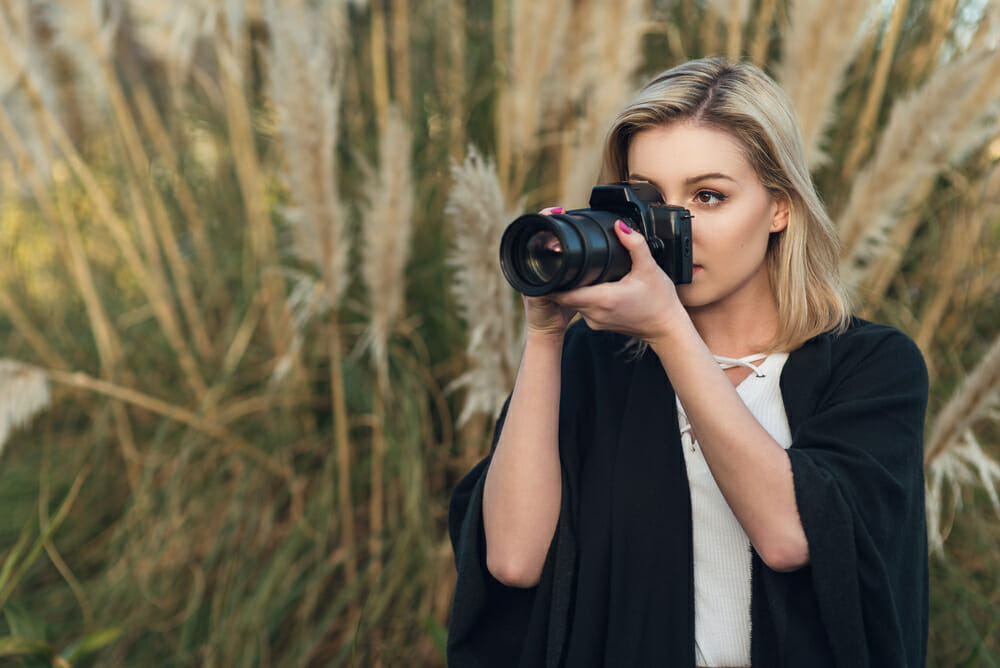 Female Photographer using a zoom lens to take a photograph